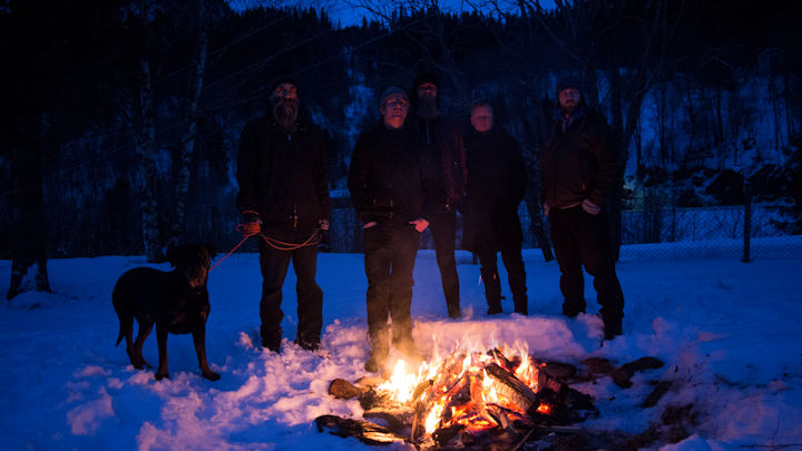 Dark photo of band members and dog by a fire in a forest